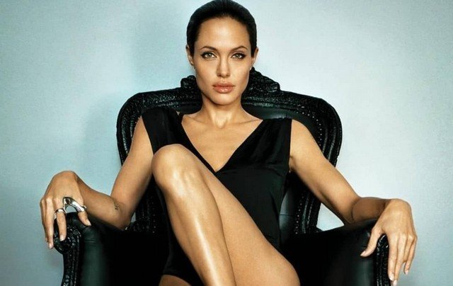 Анджелина Джоли в черном платье сидит на стуле