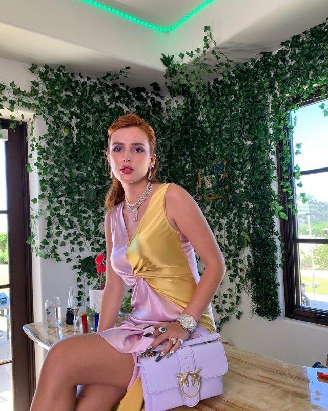 Белла Торн в разноцветном платье сидит на столе