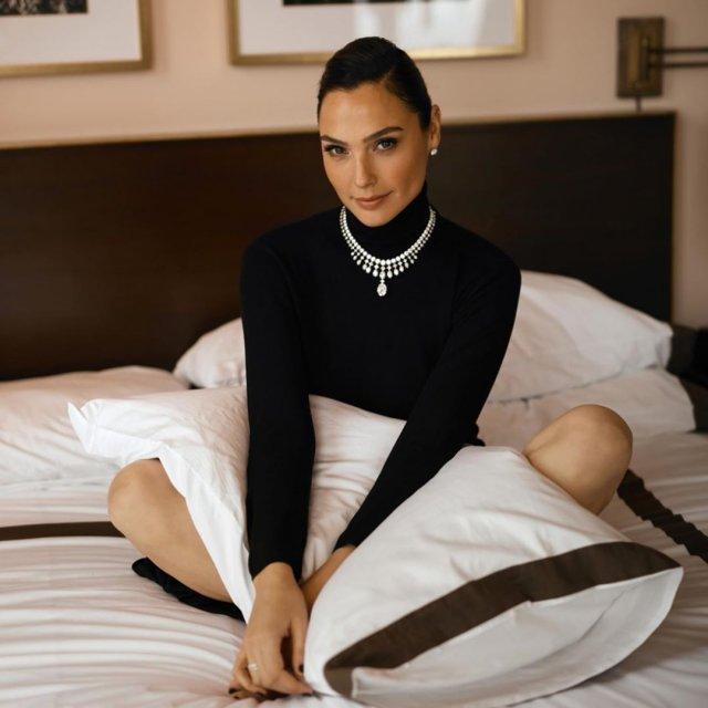 Галь Гадот в черной кофте на кровати