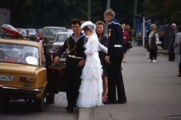 Жених и невеста садятся в машину, украшенную свадебной атрибутикой