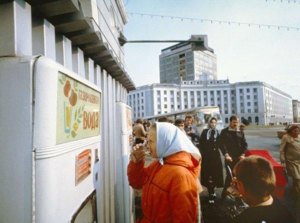 Женщина пьет воду из автомата с газировкой