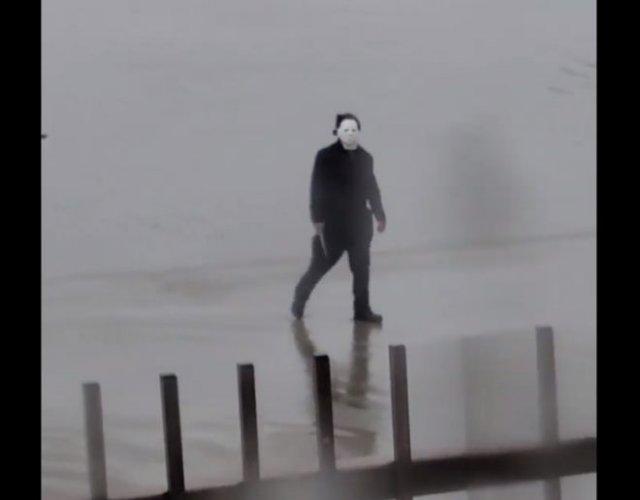 Человек в костюме Майкла Майерса, держа в руках нож, гуляет по улице и пугает местных жителей